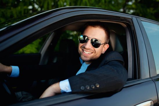 Businessman in car smiling